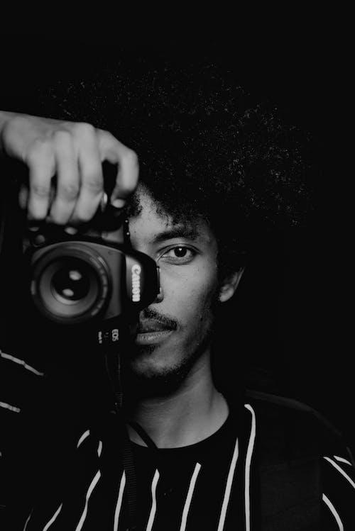 Man in Black Crew Neck Shirt Holding Black Camera