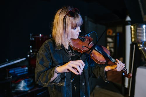 Woman in Blue Denim Jacket Playing Violin