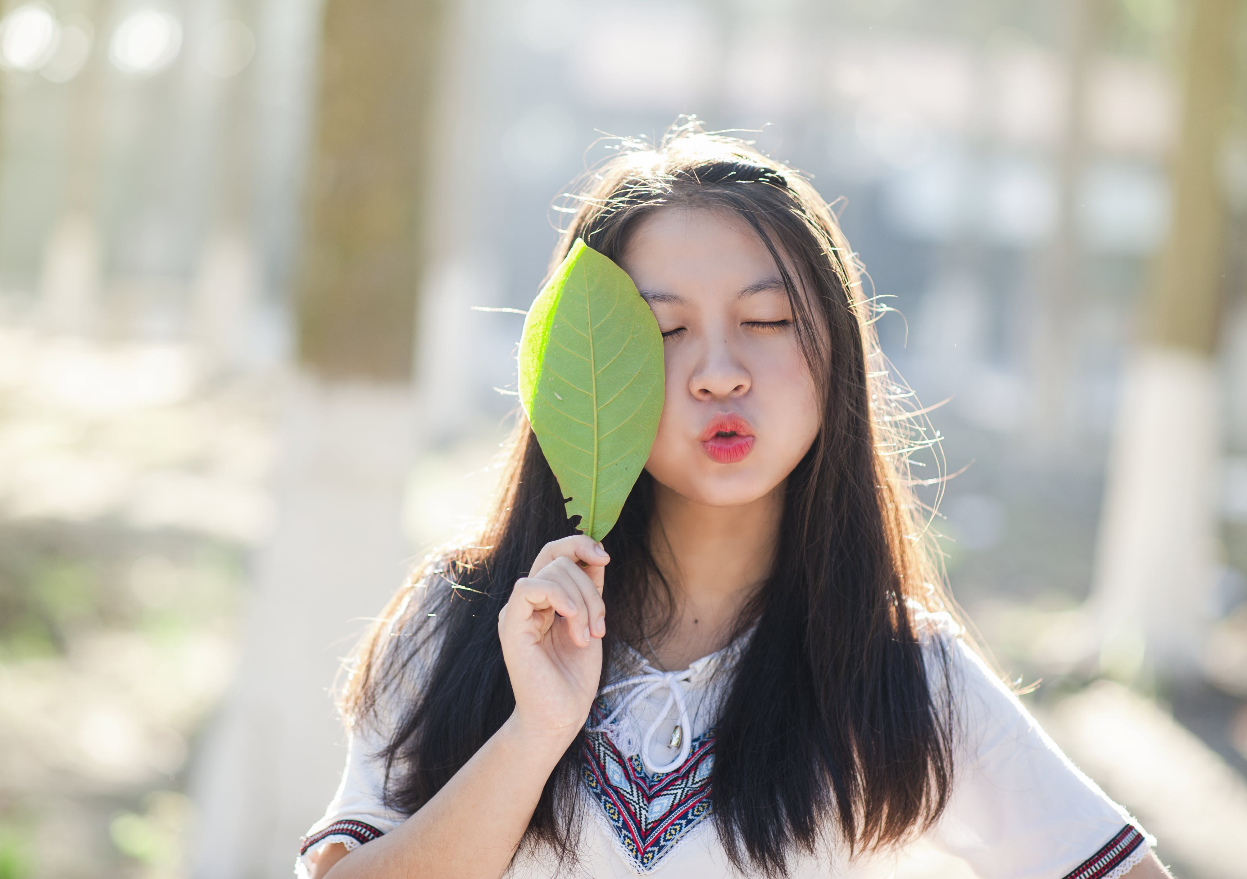 Woman Holding Green Leaf With Lips Kissing and Closing Eyes