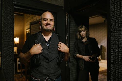 Man in Black Button Up Shirt Standing Beside Woman in Black Dress