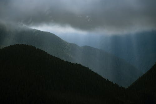 A Silhouette of a Mountain Under a Cloudy Sky