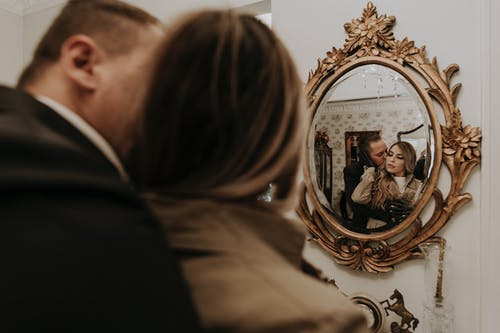 Man and Woman Kissing in Gold Framed Mirror