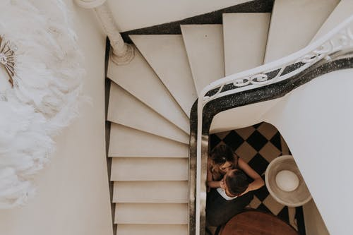 Man in Black Jacket Lying on White Spiral Staircase