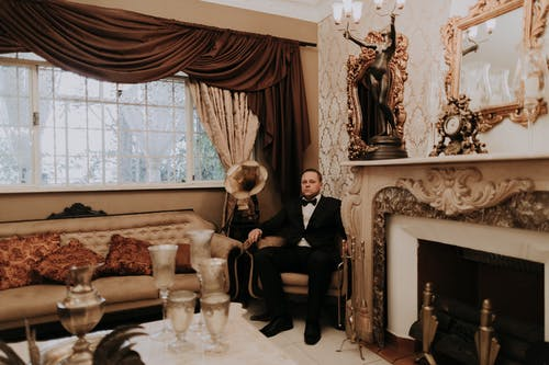 Man in Black Suit Sitting on White Sofa Chair