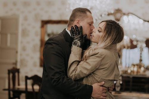 Man in Black Suit Kissing Woman in Brown Coat