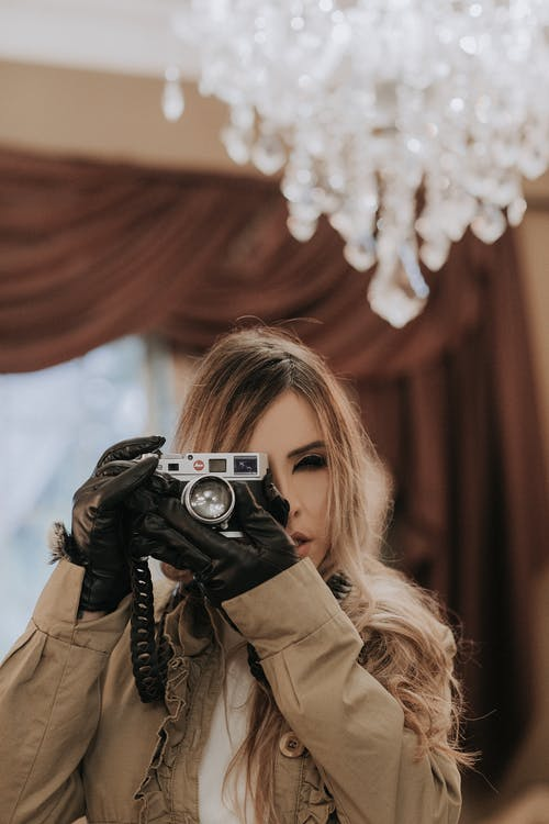 Woman in Brown Coat Holding Silver Camera