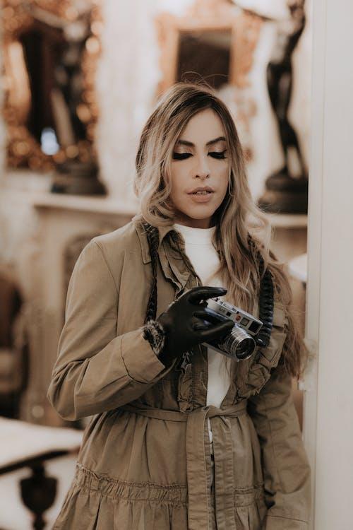 Woman in Brown Coat Holding Black Dslr Camera