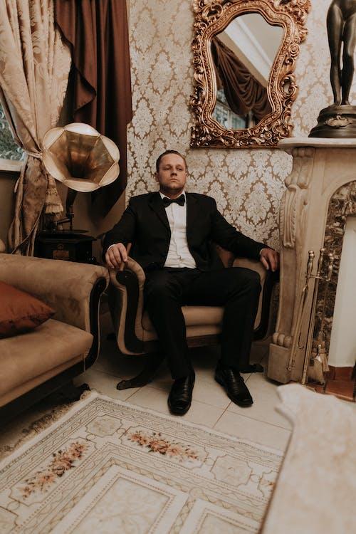 Man in Black Suit Sitting on Brown Sofa