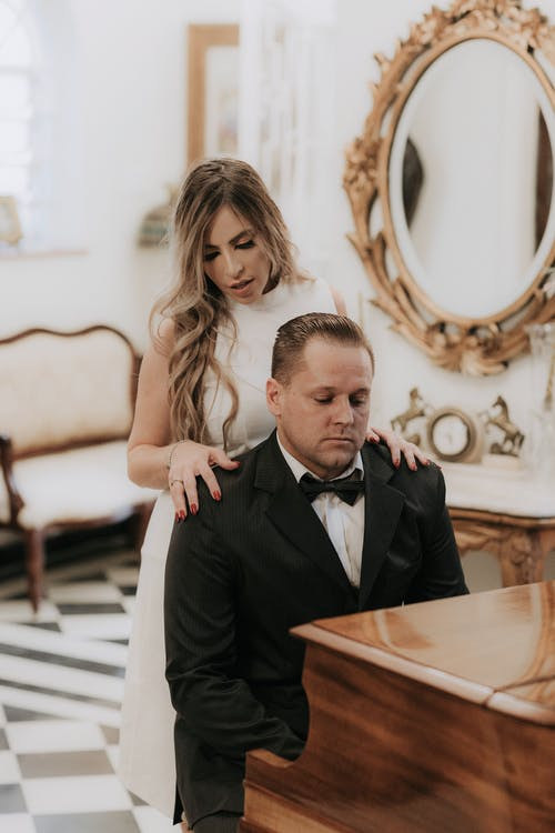 Man in Black Suit Jacket Sitting Beside Woman in White Sleeveless Dress
