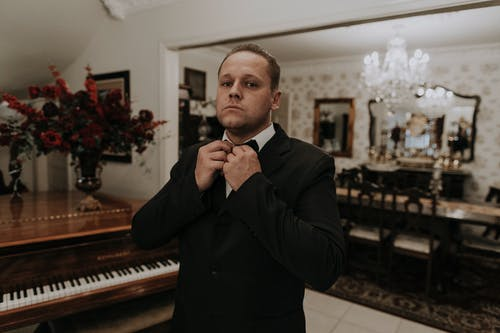 Man in Black Suit Jacket Sitting Beside Piano