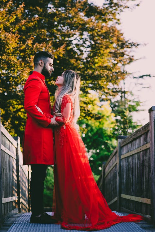 A Couple Standing on a Wooden Bridge