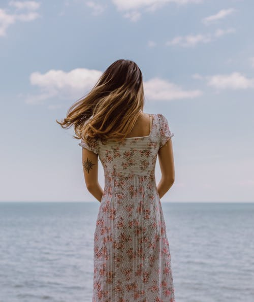 Woman in White Floral Dress Standing on Seashore