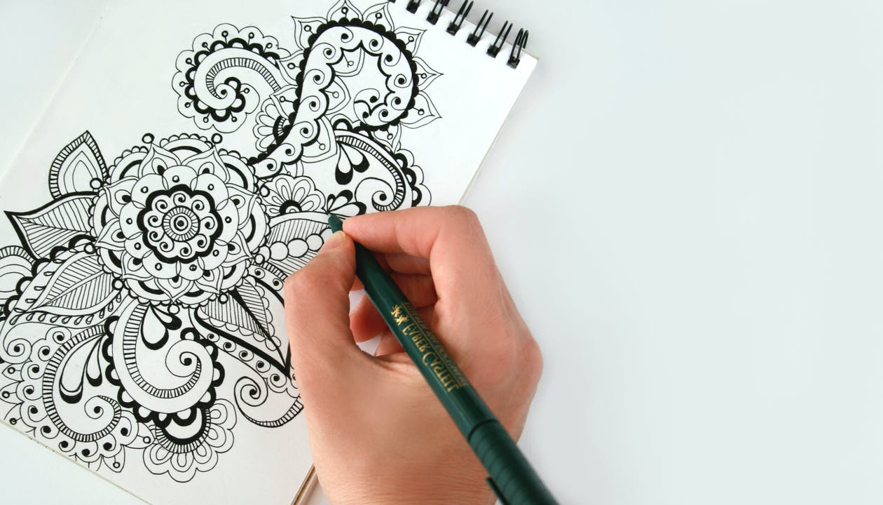 Person Holding Black Pen Sketching Flower