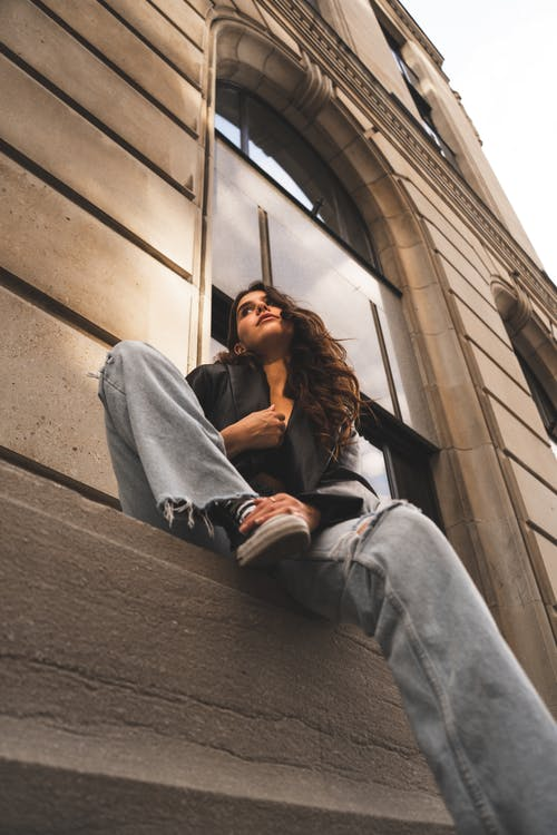 Woman in Gray Jacket and Black Pants Sitting on Stairs