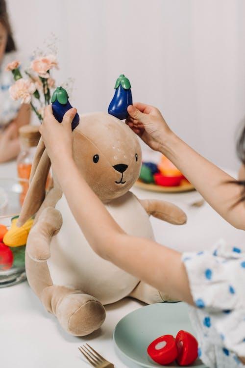 A Kid Playing with Stuffed Animal