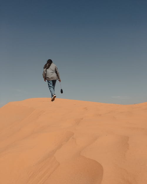 Back View of a Person Walking in a Desert