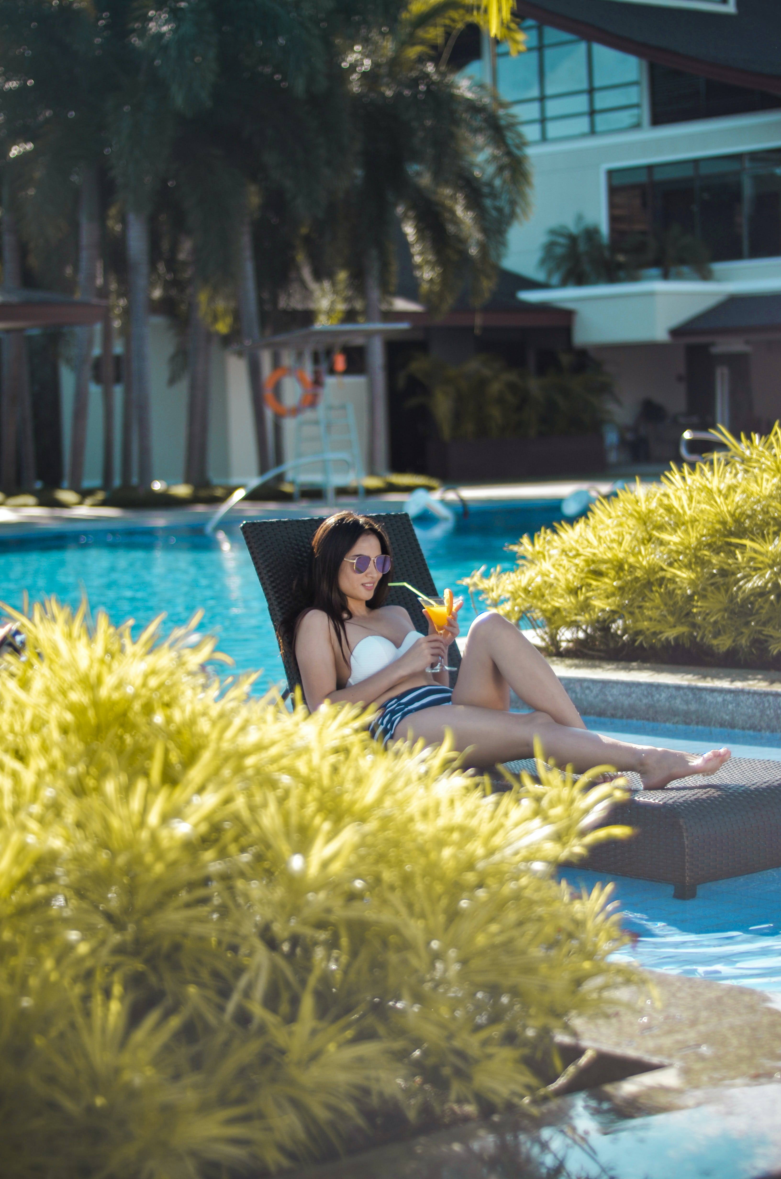 Woman Sitting on Outdoor Lounger Chair While Holding Drinking Glass