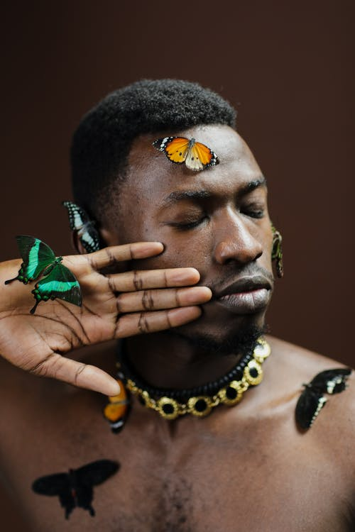 Man in Yellow Beaded Necklace Covering His Mouth With Green and Yellow Butterfly