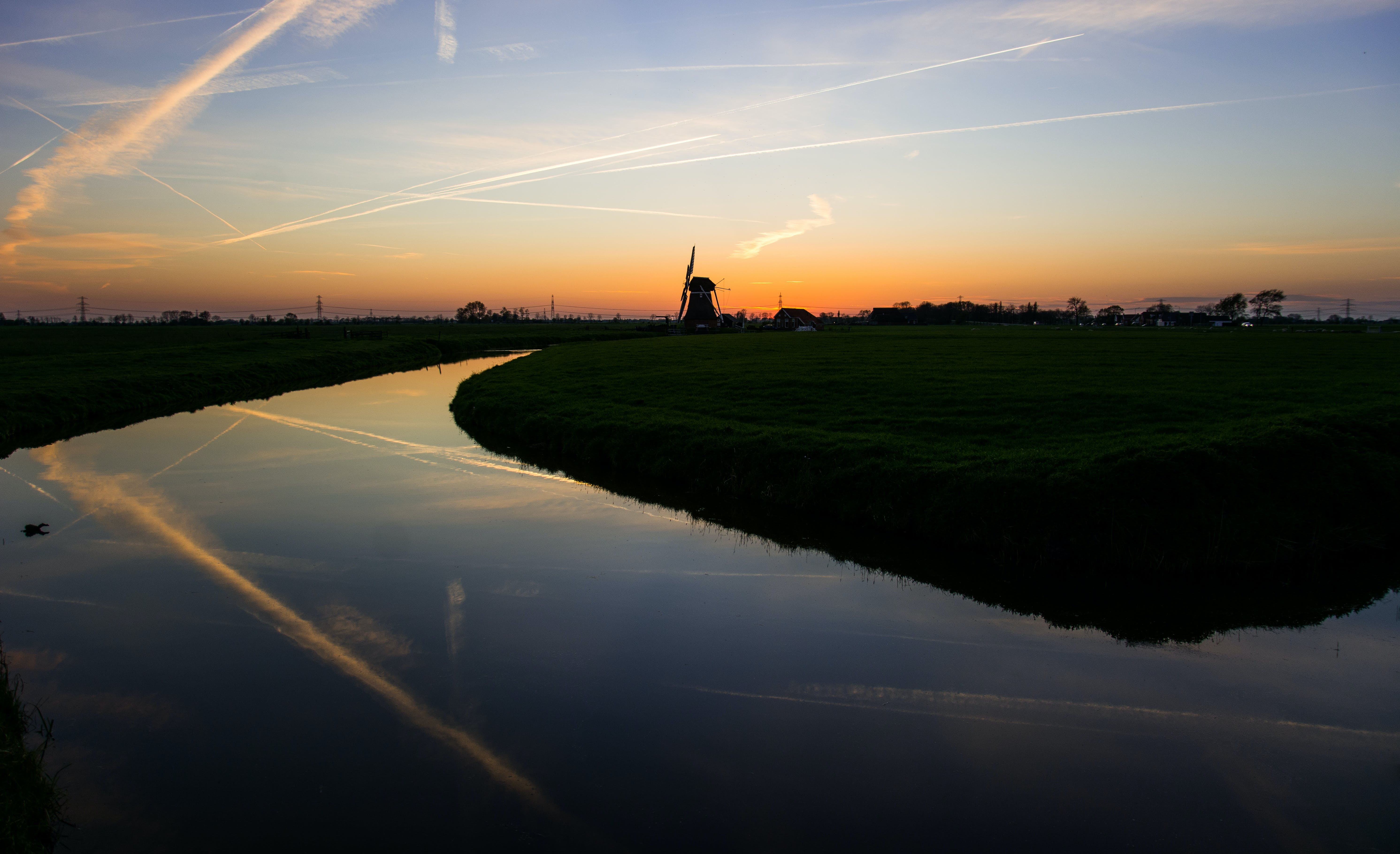 Body of Water With Windmill in Vicinity