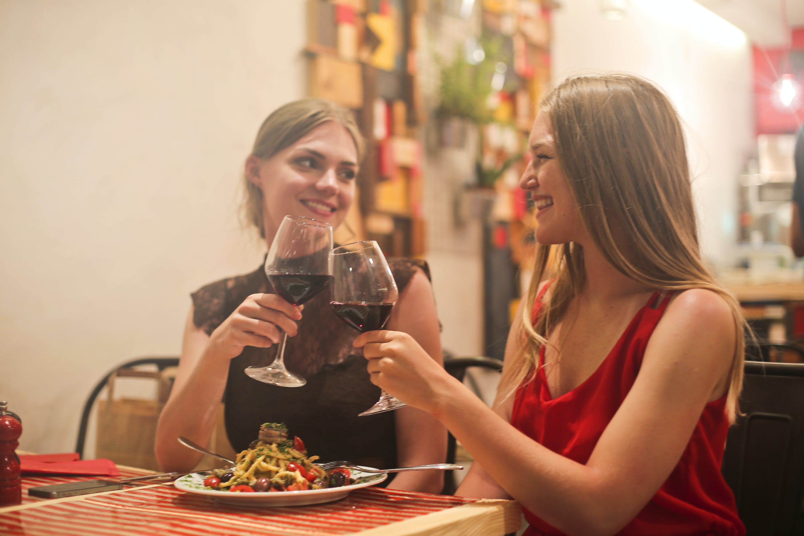 Two Women Holding Long-stem Wine Glasses With Red Liquid