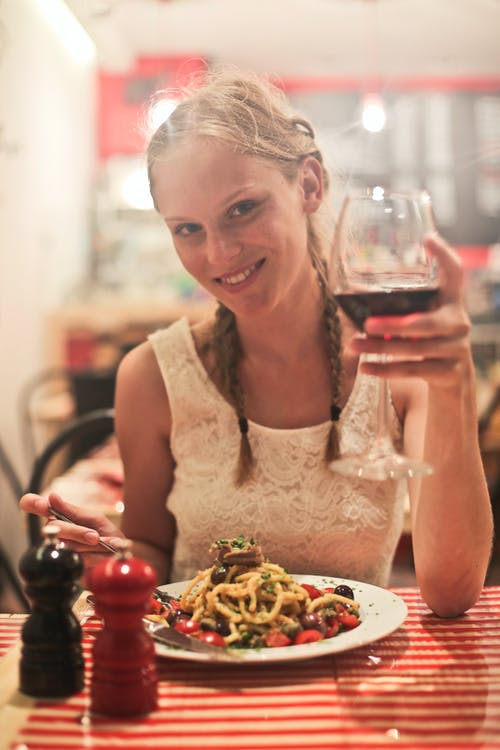 Woman in White Sleeveless Tops Holding Wine Glass