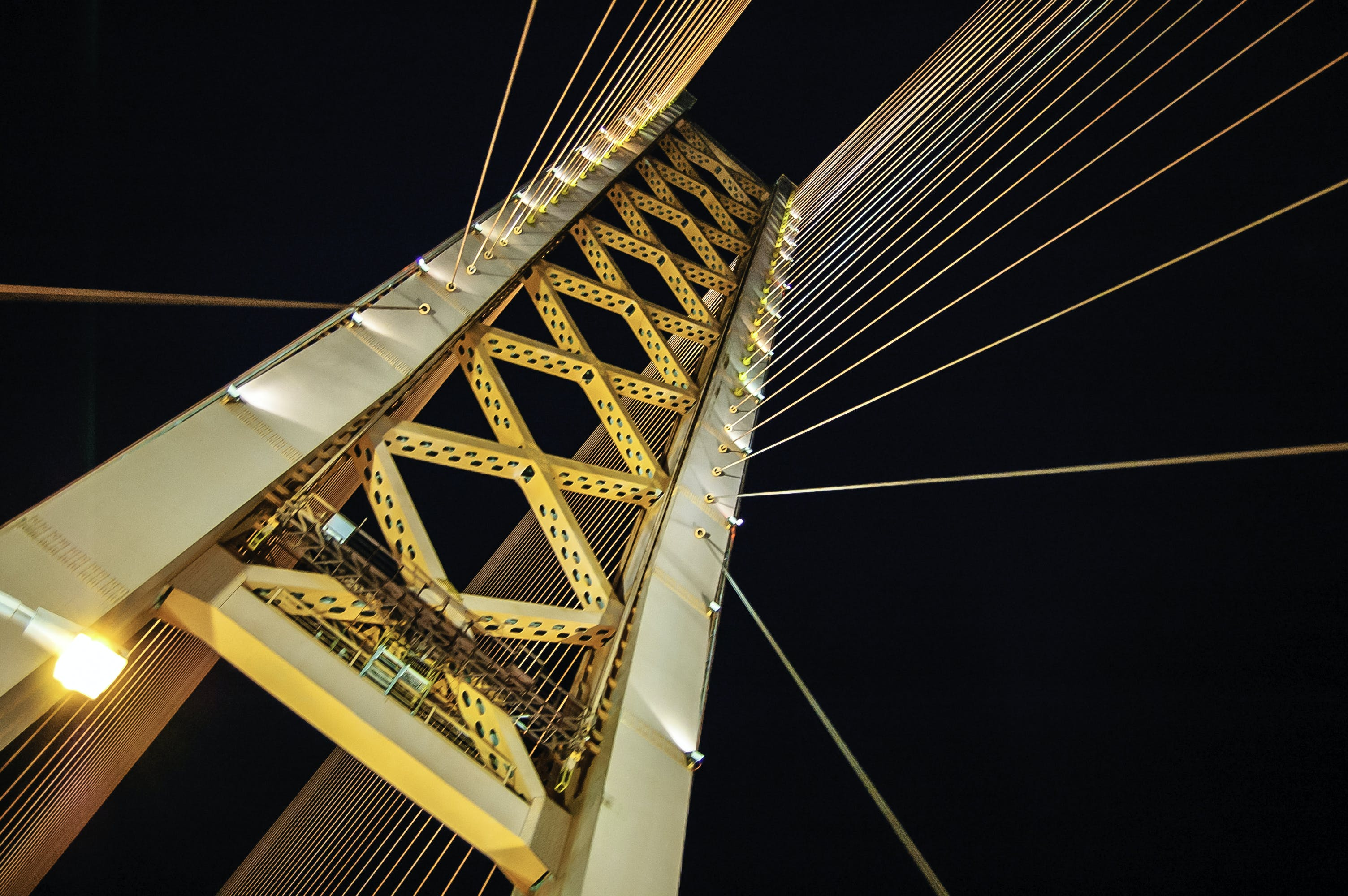 Low Angle Photography of White and Yellow Suspension Bridge at Nighttime