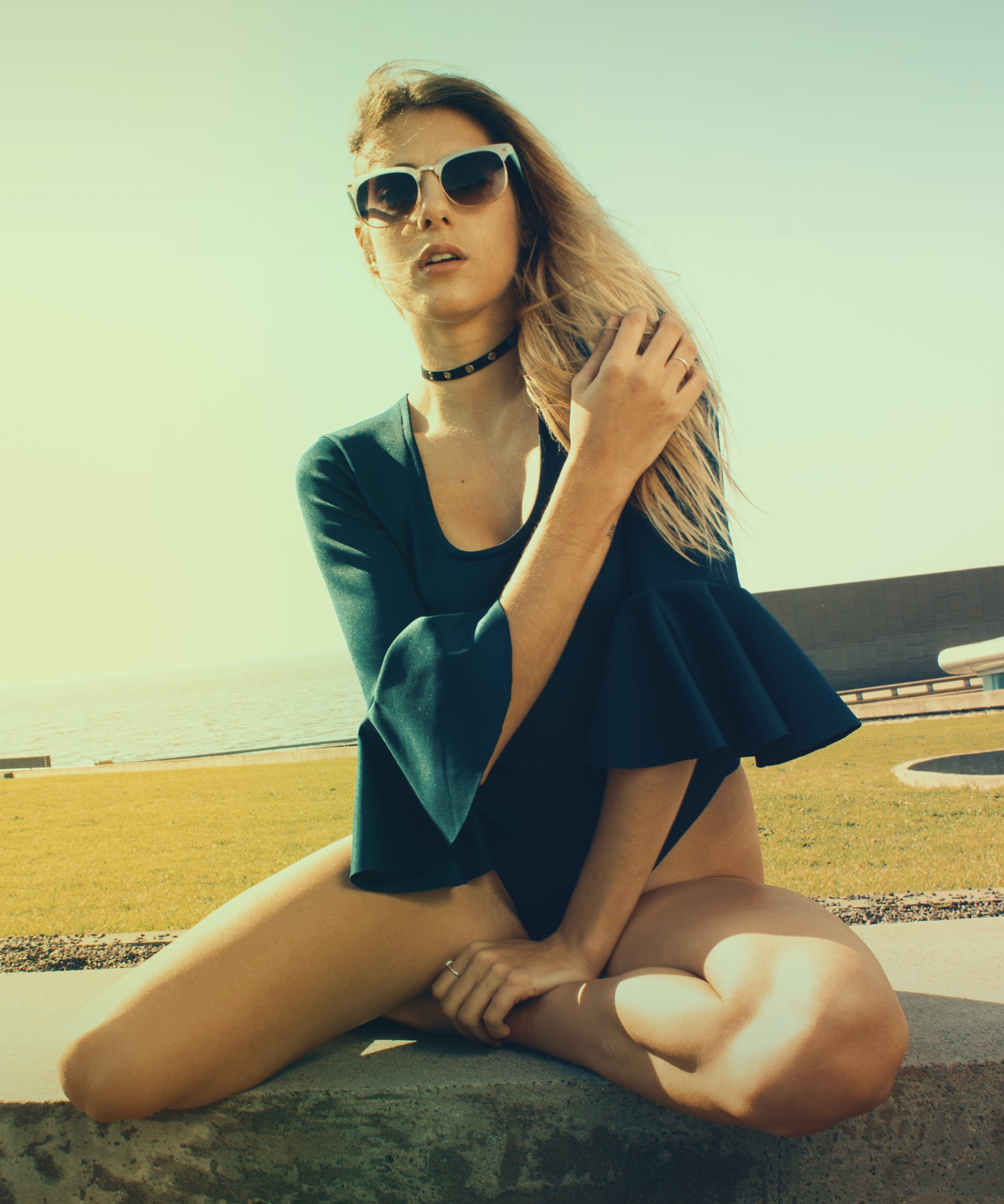 Woman Wearing Sunglasses and Blue Blouse during Photography Under Sunset