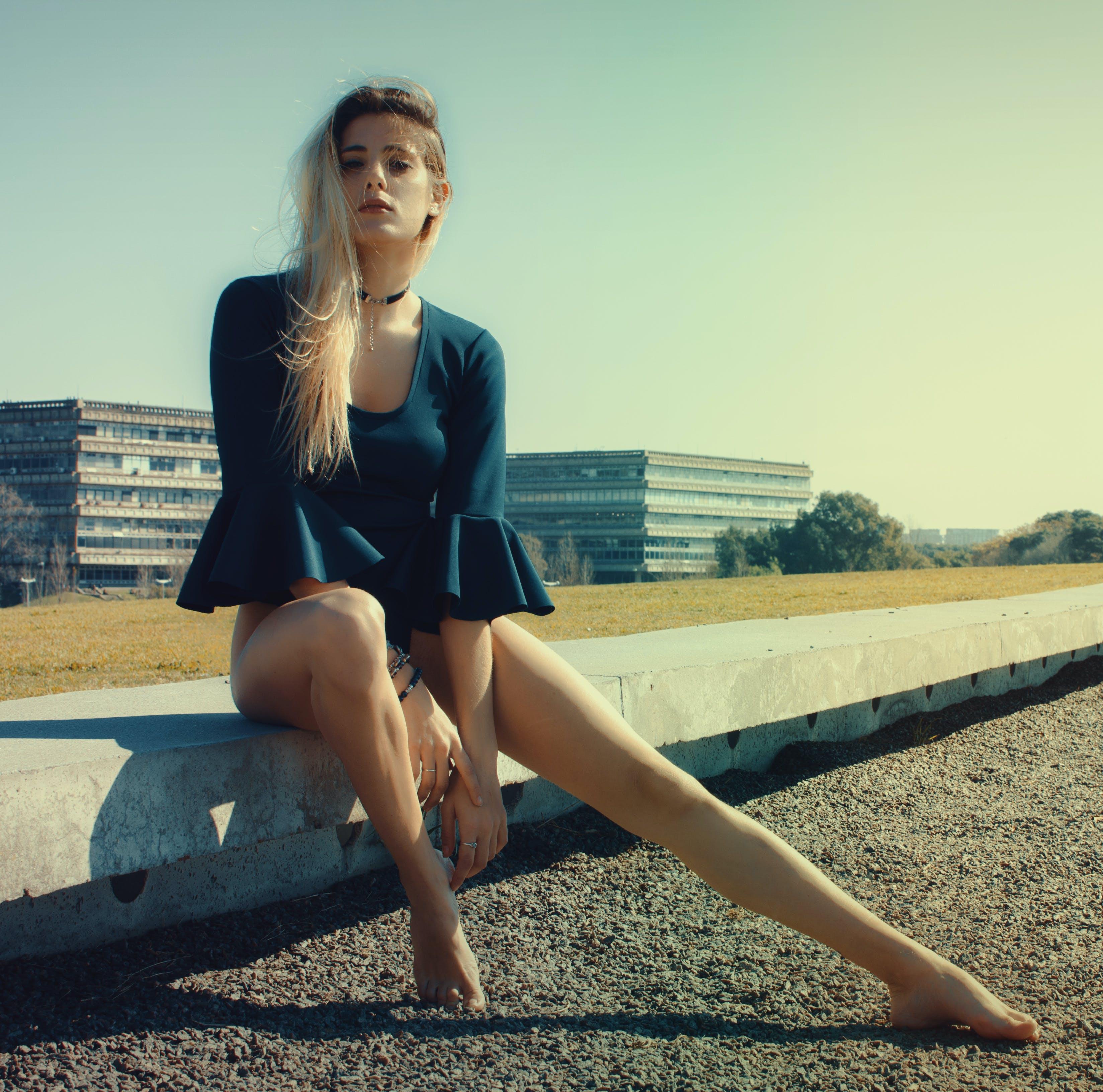Woman Wears Black Scoop-neck Long-sleeved Blouse Seats on Grey Concrete Pavement