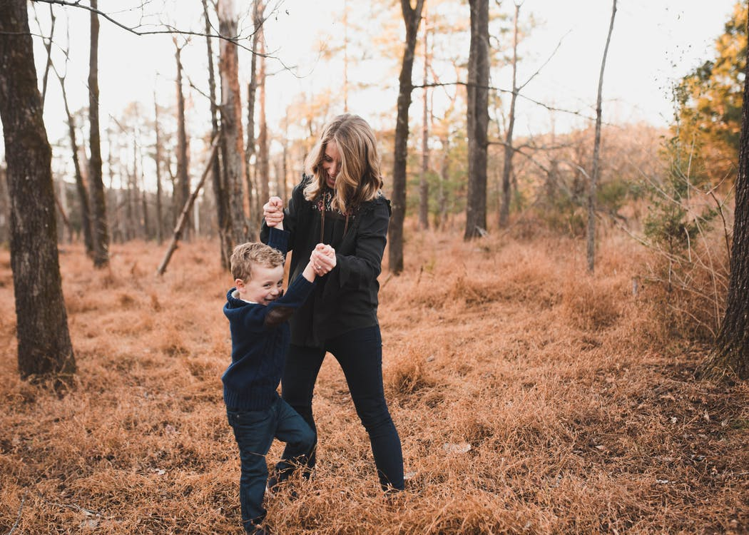 Woman Wearing Black Jacket Playing With Young Boy