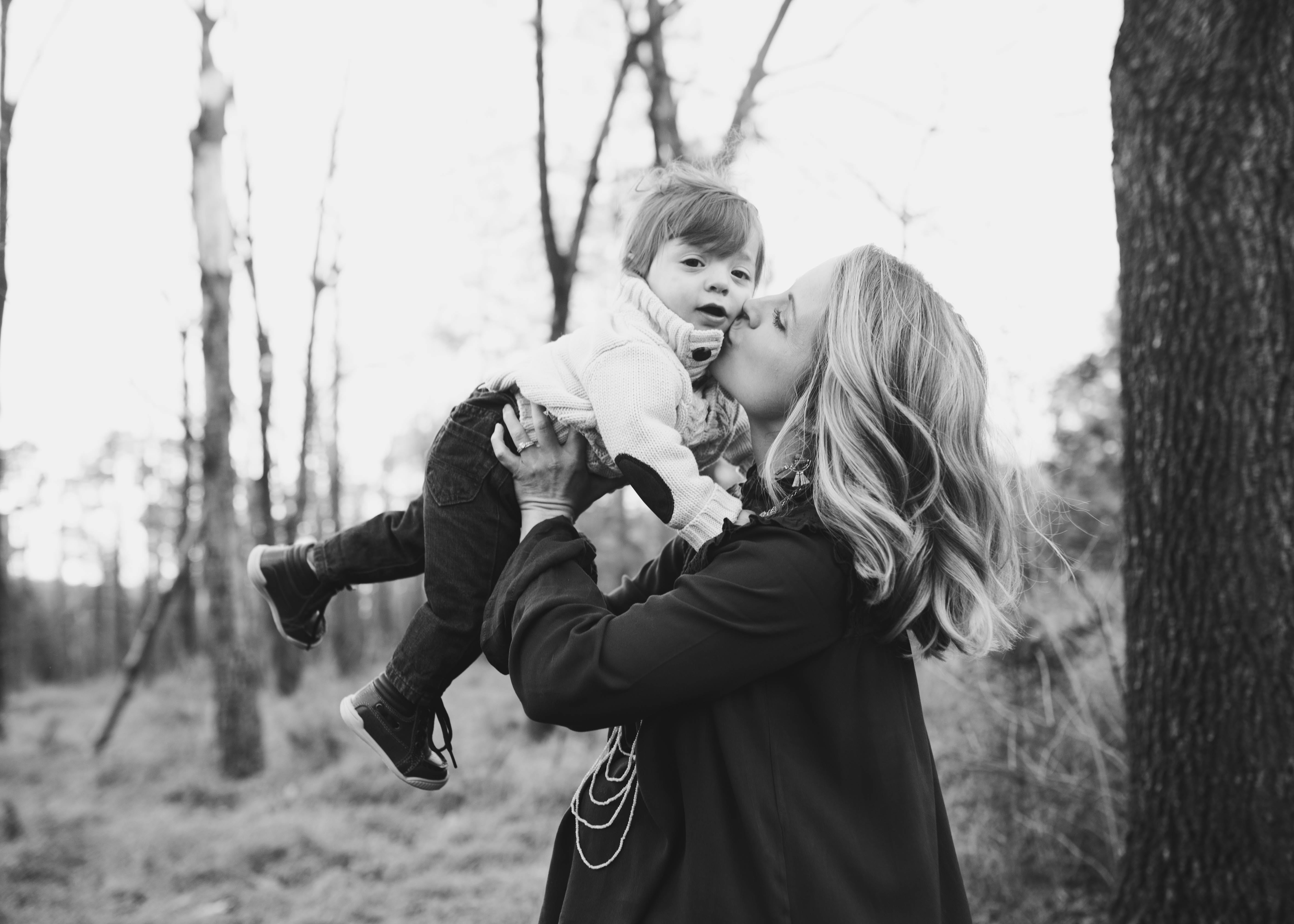 Grayscale Photo Of Woman Kissing Toddler On Cheek