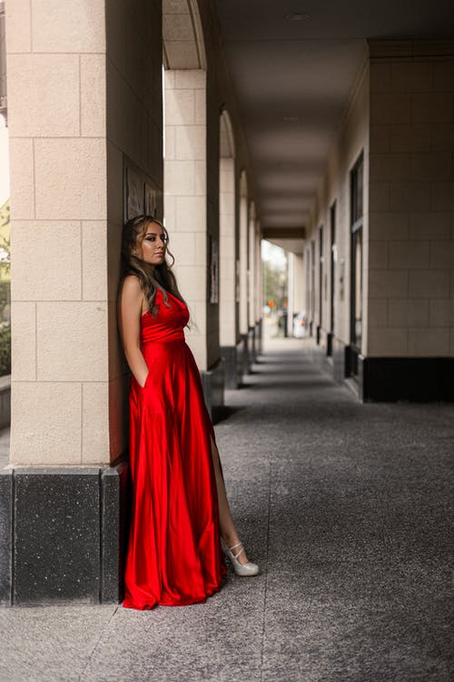 Woman in Red Sleeveless Dress Standing on Hallway