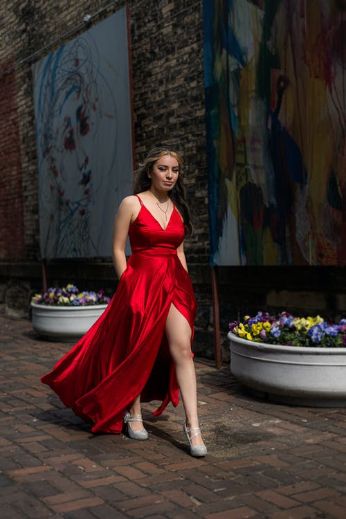 Woman in Red Tube Dress Standing Near Flowers
