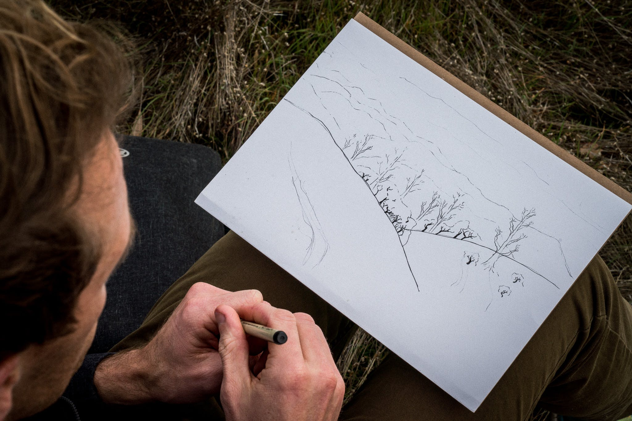 Man Drawing Mountain and Trees