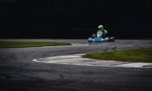 Man Wearing Green Helmet Riding Go Kart