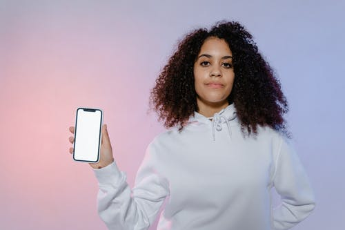 Woman in White Long Sleeve Shirt Holding White Mobile Phone
