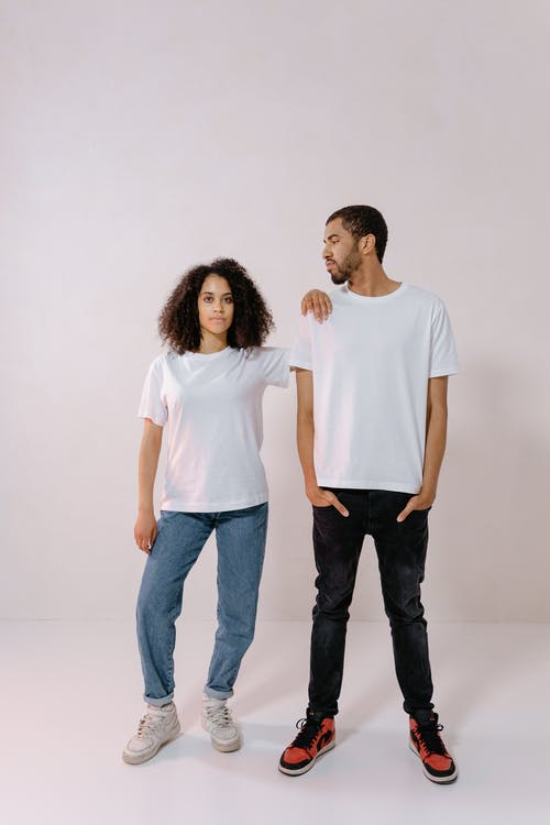 Man in White T-shirt and Black Denim Jeans Standing Beside Woman in White T-Shirt and Blue Jeans