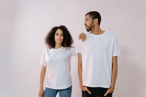 Man in White T-shirt Looking at Woman in White T-Shirt