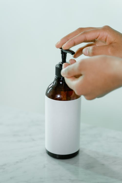 Person Holding White and Brown Bottle