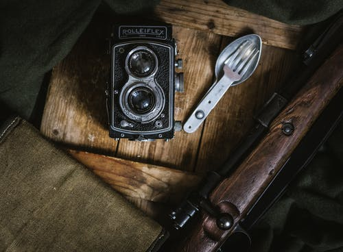 Gray and Black Rolleiflex Camera Beside Fork and Spoon Decor