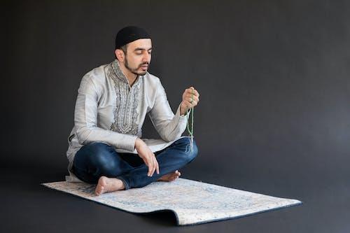 Man in White Dress Shirt and Blue Denim Jeans Sitting on Black Floor