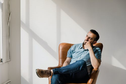 Man in Blue Crew Neck T-shirt and Blue Denim Jeans Sitting on Brown Leather Armchair