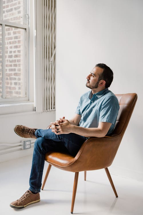 Man in Blue Dress Shirt Sitting on Brown Leather Chair