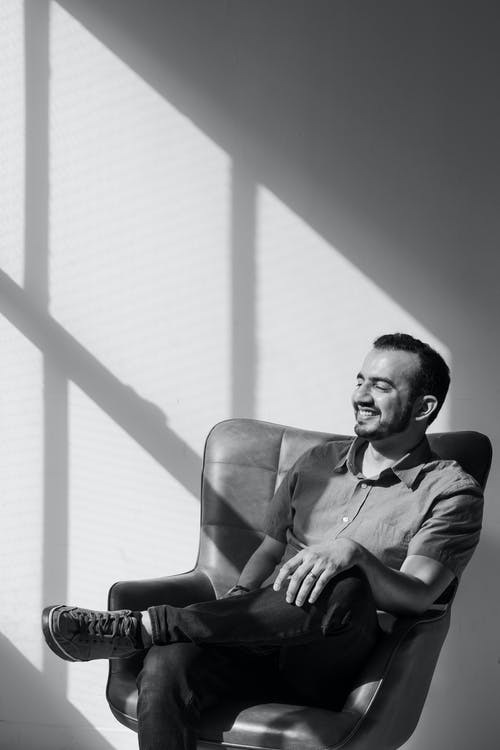 Black and White Photo of Man Sitting on a Chair