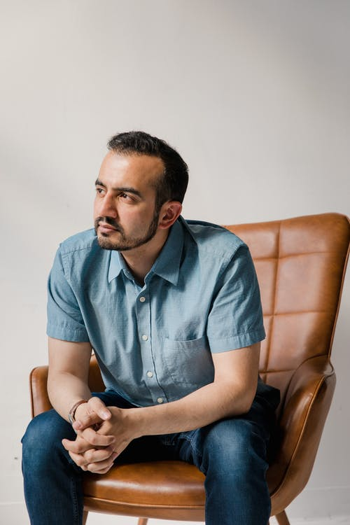 Man in Blue Button Up Shirt Sitting on Brown Leather Armchair