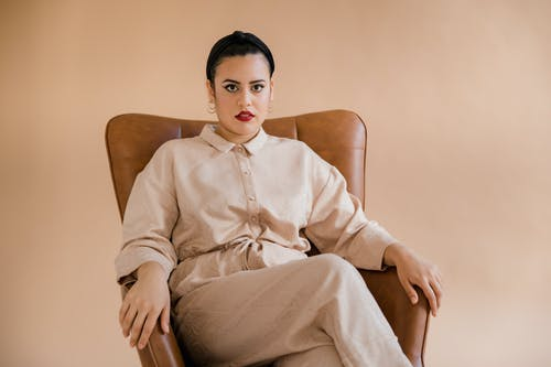 Woman in White Dress Shirt Sitting on Brown Chair