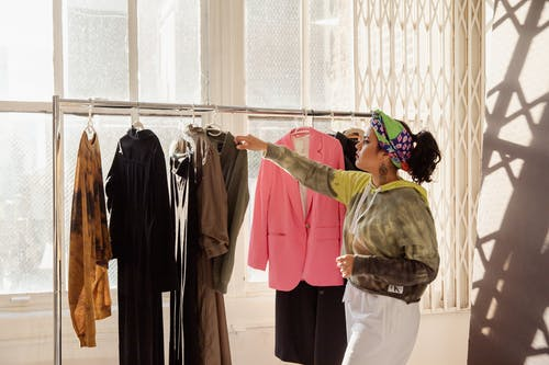 Woman in Brown Jacket Standing Near Clothes Rack