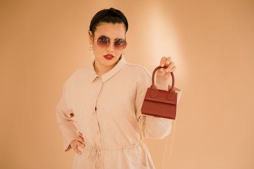 Woman in White Button Up Long Sleeve Shirt Holding Brown Leather Handbag
