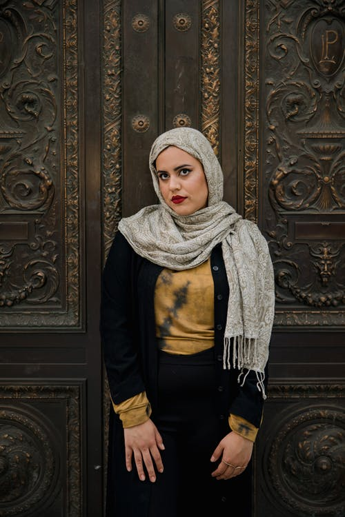 Woman in Black Long Sleeve Shirt and White Hijab Standing by the Door