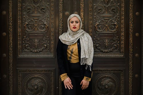 Woman in Black Long Sleeve Shirt and Hijab Standing Beside a Door
