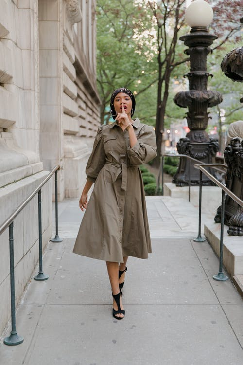 Woman in Brown Coat Standing Near White Concrete Pillar